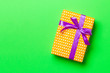 Leinwandbild Motiv Top view Christmas present box with purple bow on green background with copy space