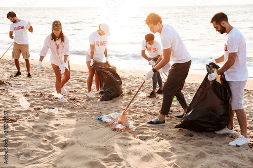 Fototapeta  Image of acive voluntary workers cleaning beach from plastic at seashore