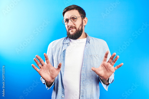 Obraz na plátne Bearded Caucasian man in glasses with disgust looks at camera with arms extended