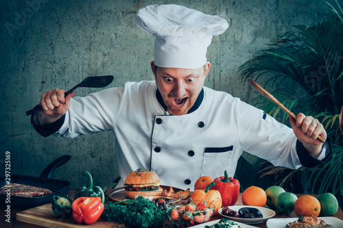 Obraz na plátně  Funny chef looking at food on the wood table exciteing mood