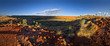 canvas print picture - Large meteorite crater at the outback Australia – Wolf Creek crater with spinifex grass and boulders and blue sky as background in the morning sun
