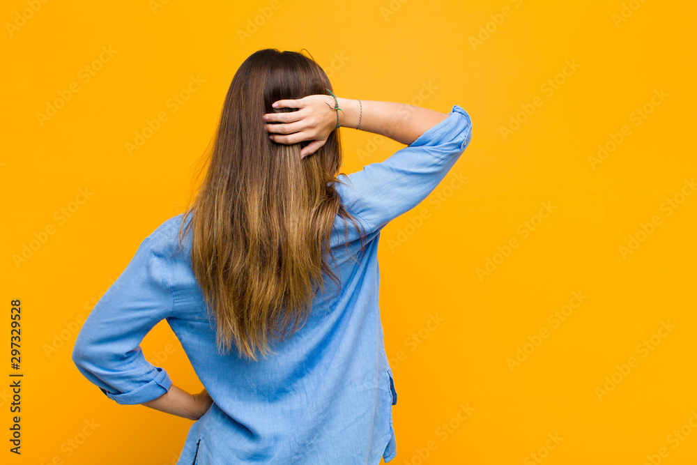 Fototapety, obrazy: young pretty woman thinking or doubting, scratching head, feeling puzzled and confused, back or rear view against orange wall
