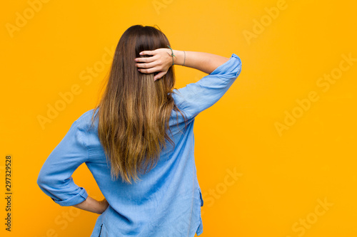 young pretty woman thinking or doubting, scratching head, feeling puzzled and confused, back or rear view against orange wall