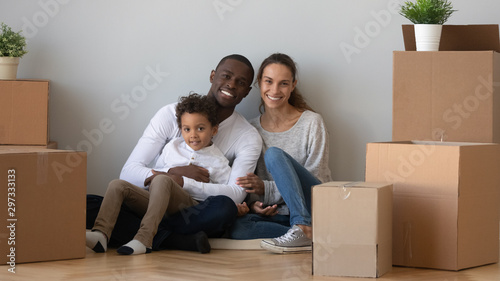 Photo Portrait of happy multiracial family relocating to new home