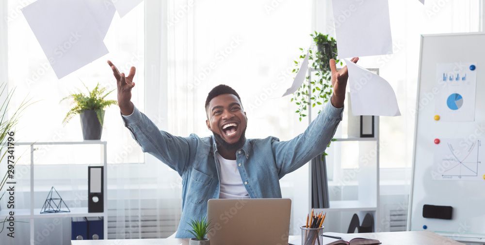 Fototapeta Cheerful african american employee celebrating success throwing papers in office
