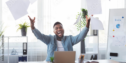 Fotografering Cheerful african american employee celebrating success throwing papers in office