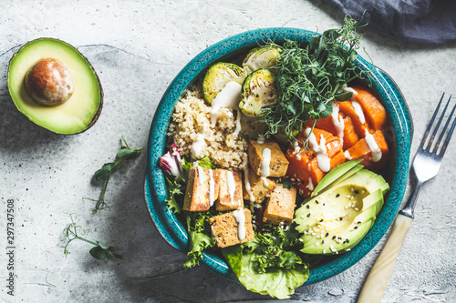 Photo Buddha bowl with quinoa, tofu, avocado, sweet potato, brussels sprouts and tahini dressing, top view