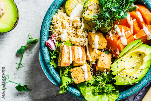 Fotografía  Buddha bowl with quinoa, tofu, avocado, sweet potato, brussels sprouts and tahini dressing, top view