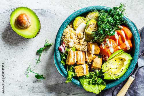 Foto Buddha bowl with quinoa, tofu, avocado, sweet potato, brussels sprouts and tahini dressing, top view