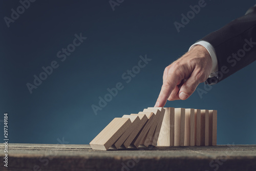 Fototapeta Business crisis manager stopping collapsing dominos with his finger