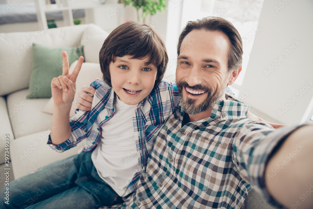 Fototapety, obrazy: Comfortable weekend vacation with father concept. Close up photo of handsome bearded with teeth smile guy hugging his sweet son taking selfie making v-sign in living room house indoors