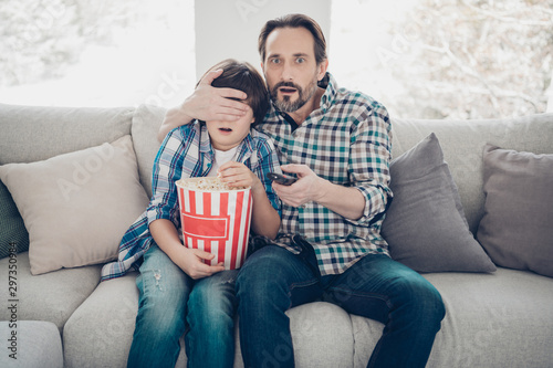 Its forbidden for little kids to watch this program concept. Photo of excited shocked amazed surprised mature daddy closing eyes to his offspring changing channel