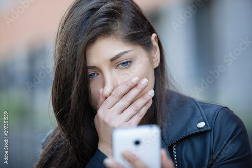 Woman looks at a smartphone. Tablou Canvas