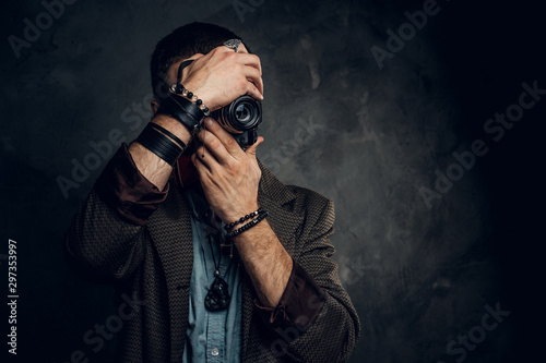 Pinturas sobre lienzo  Focused young photographer is taking a photo on the dark grunge background