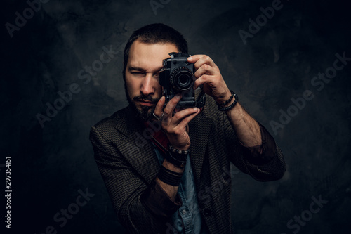 Fotografía  Focused young photographer is taking a photo on the dark grunge background
