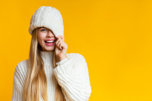 Playful Girl Covering Her Eye With Knitted Hat