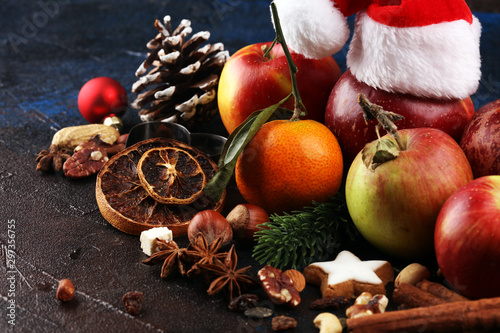 obraz PCV christmas cookies and santa had with spieses, nuts and fruits on rustic table