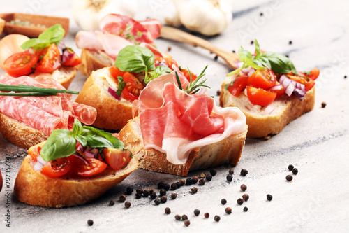 Assorted bruschetta with various toppings. Appetizing bruschetta or crudo crostini. Variety of small sandwiches. Mix bruschetta on table - 297357747