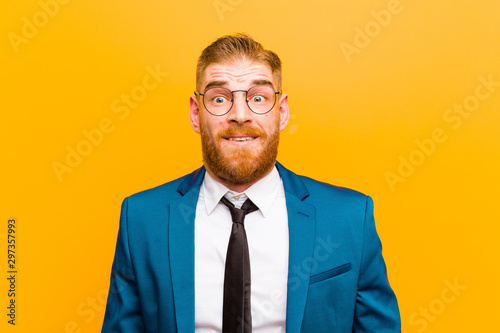 Fotografía  young red head businessman feeling terrified and shocked, with mouth wide open i