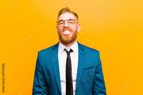 Obraz na plátně  young red head businessman feeling disgusted and irritated, sticking tongue out,