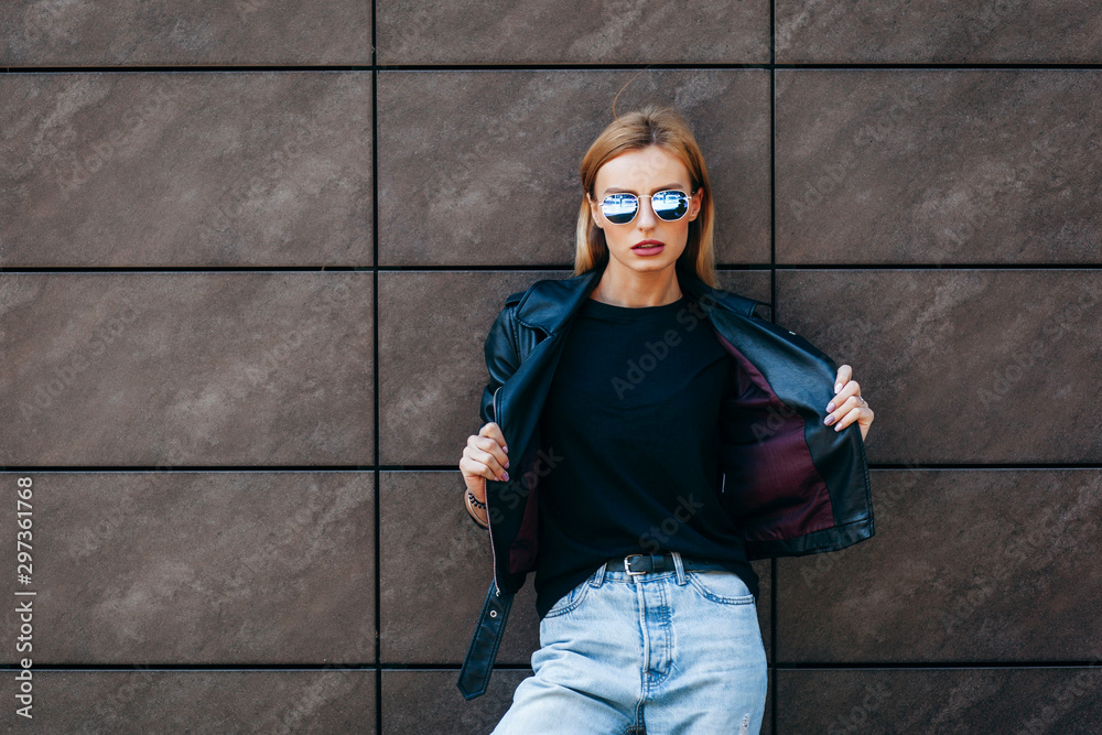 Fototapety, obrazy: Girl wearing t-shirt, glasses and leather jacket posing against street , urban clothing style. Street photography