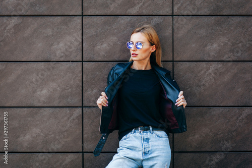 plakat Girl wearing t-shirt, glasses and leather jacket posing against street , urban clothing style. Street photography