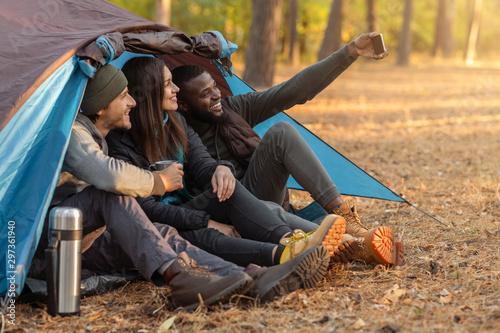 Foto op Canvas Kamperen Group of tourists taking selfie in camping tent