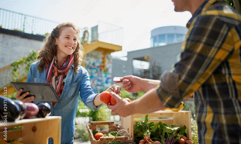 Fototapeta Friendly woman tending an organic vegetable stall at a farmer's