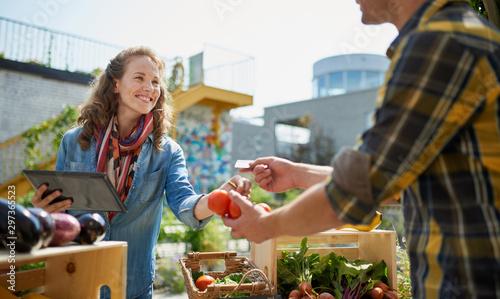 Friendly woman tending an organic vegetable stall at a farmer's Canvas