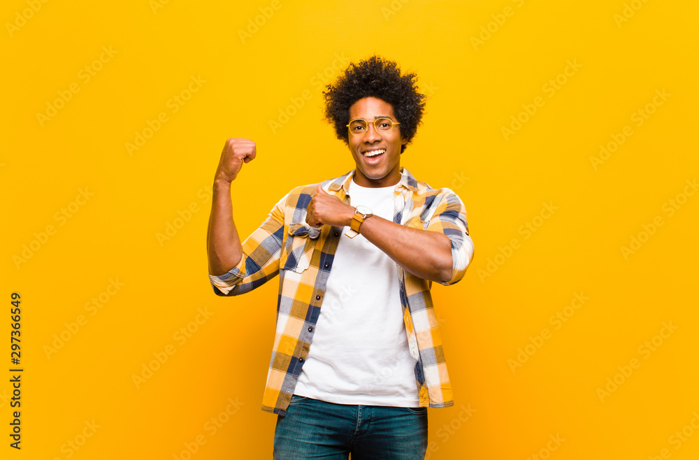 Fototapety, obrazy: young black man smiling cheerfully and casually pointing to copy space on the side, feeling happy and satisfied against orange wall