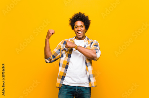 Fotografia  young black man smiling cheerfully and casually pointing to copy space on the si