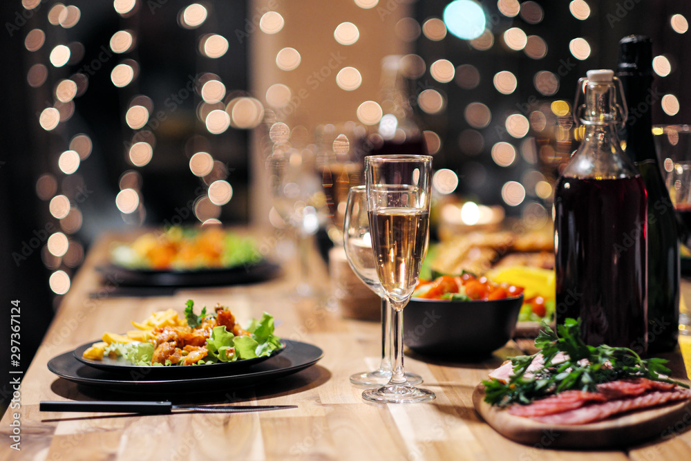 Fototapety, obrazy: Festive table setting. Food and drinks, plates and glasses. Evening lights and candles. New Year's Eve.