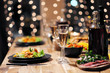 canvas print picture - Festive table setting. Food and drinks, plates and glasses. Evening lights and candles. New Year's Eve.
