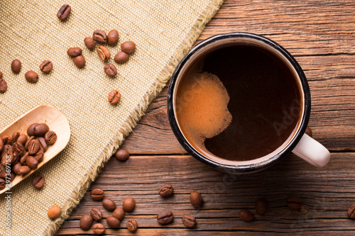 Keuken foto achterwand Cafe Coffee mug and coffee beans on a wooden background. Vintage iron mug filled with hot freshly brewed coffee.