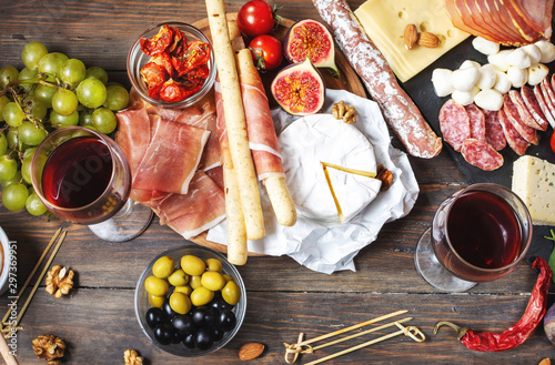 Italian antipasto with prosciutto, ham, cheese, olives and grissini breadsticks on wooden background Canvas Print