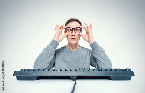 Funny man holds glasses in his hands while sitting at a keyboard in front of a c Fototapet