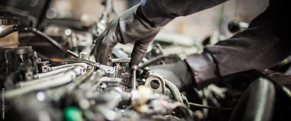 Fototapeta Close up of car mechanic repairer technician repairs auto engine