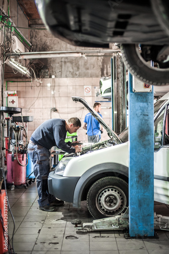 Two car mechanic repairers service technician repairs auto engine