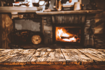 Table top with fireplace background in cozy home interior.