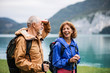 A senior pensioner couple hiking by lake in nature, talking.