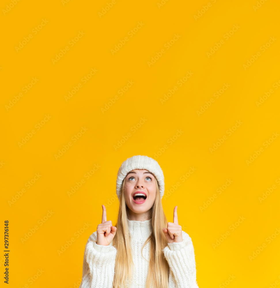 Fototapety, obrazy: Amazed girl in white hat pointing up at copy space