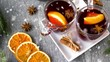 christmas and seasonal drinks concept - snowing over glasses of hot mulled wine with orange slices, aromatic spices and fir branch on grey background