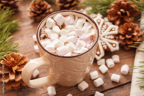 Photo sur Toile Chocolat A beige Cup of traditional Christmas hot chocolate or cocoa with marshmallow. Christmas gingerbread on wooden background