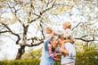 Leinwandbild Motiv Senior grandparents with grandchildren standing under tree in blossom in spring.