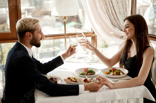 Romantic date of a handsome young man and attractive brunette girl at the restau Canvas Print