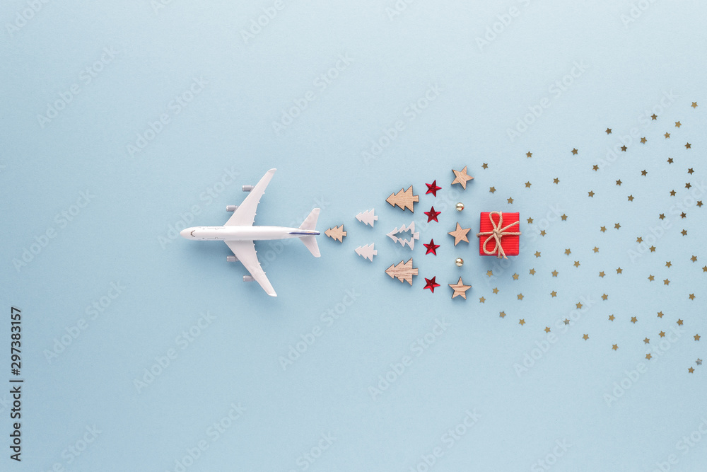 Christmas composition. Airplane flying in sky star gift bauble set top view background with copy space for your text. Flat lay.