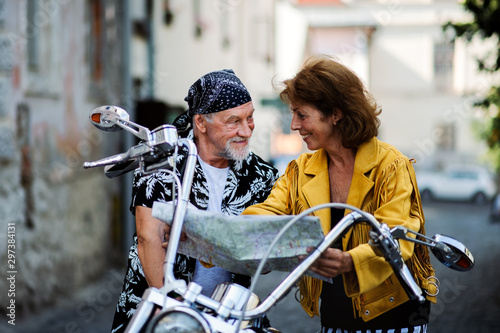 Fotografía  A cheerful senior couple travellers with motorbike in town, looking at map