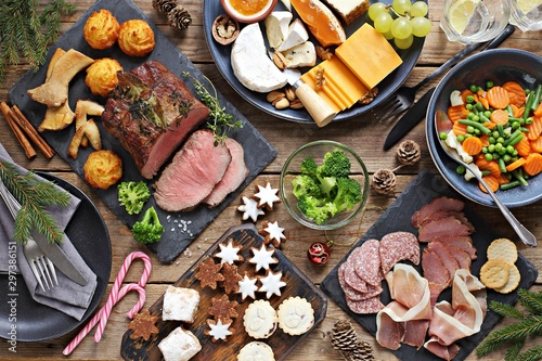 Christmas dinner table with roast beef, appetizers platter and traditional cookies. Christmass celebration, festive family dinner.  Overhead view. - 297386151
