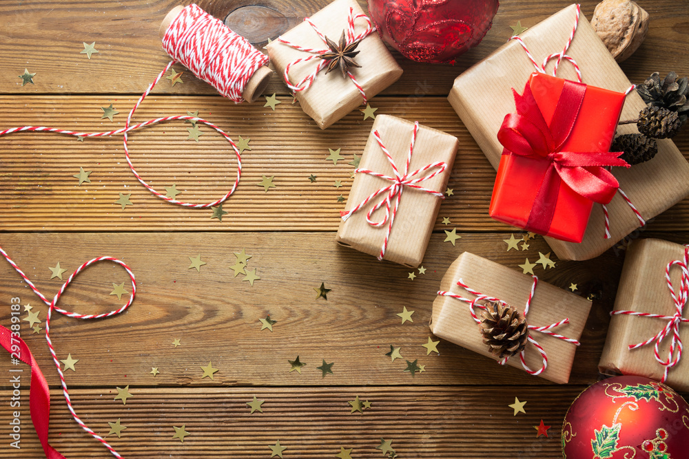 Fototapety, obrazy: Christmas background with gift boxes wraped in craft paper over wooden table prepared for celebrating festive holiday season. Copy space.