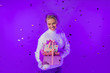 canvas print picture - Girl holding a gift and laughing merrily. Metallic shiny confetti falls from above. A blonde girl in fluffy mittens and a white sweater on a bright purple isolated neon background. Neon party light. G